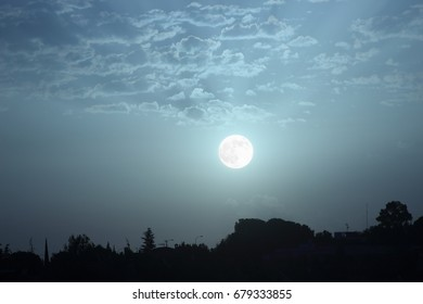 Photograph of the full moon at dawn, Moon rising over landscape with blue light,