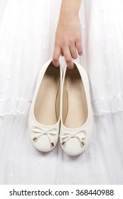 Photograph of the hand of a girl holding her white shoes the day of her first, birthday or her sweet sixteen party.