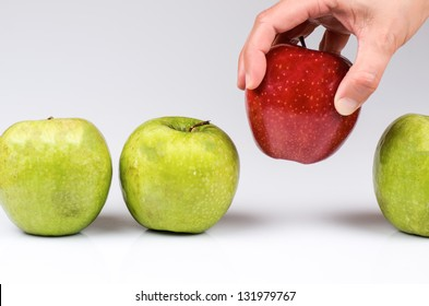 photograph of a hand picking apples to choose