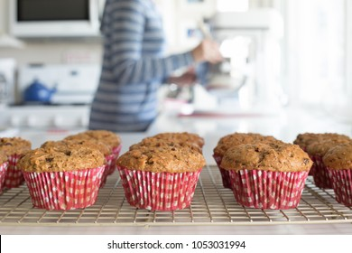 Photograph of homemade bran muffins with a women baking in the background