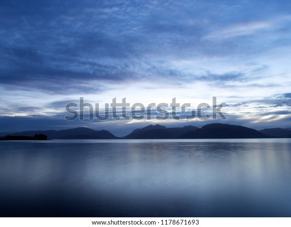 Photograph looking west across Loch Linnhe, Scotland in the early evening. The dark water has subtle reflections of the long exposure blurred clouds and the dark hills in the background.
