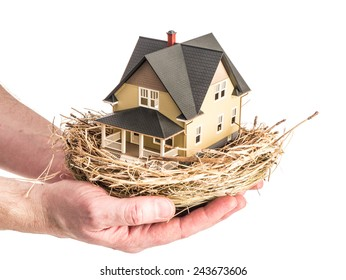 Photograph of a man holding a bird's nest with a miniature home in the nest, illustrating the concept of real estate investment as part of a retirement plan.