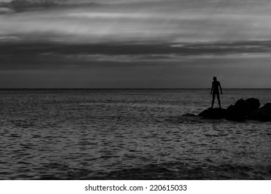 Photograph of the man on the rocks. Silhouette. Black and white photo.
