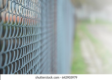 A photograph of a metal net used as a fence of private possessions. Old metal grid in perspective with a blurred background