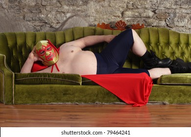 Photograph of a Mexican wrestler or Luchador lying on a green couch waiting for his match to begin.