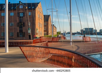 Photograph of modern circle Bridge in Copenhagen, Denmark. Harbor with new circle bridge. Bridge with several circles, in shapes, form of masts. Red handrails and fences. Houses and sky on background.