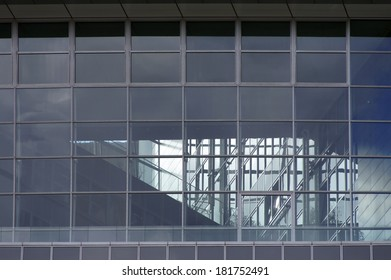 The photograph of a modern house facade with a staircase behind glass / Stairs behind glass