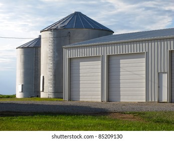 Photograph of a modern steel garage and two silos on a working farm.