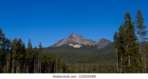Photograph of Mount Thielsen on a sunny clear day with vivid blue skies and green forest