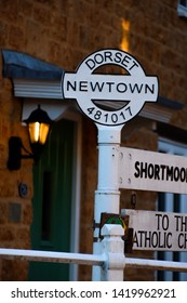 Photograph of the Newtown sign within Beaminster with signs to different places. There is also a nice dim lighting effect in the background of the shot being a persons porch light.