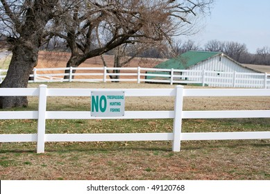 A photograph of a No Trespassing Hunting Fishing sign of a vinyl white fence with a barn in the background.