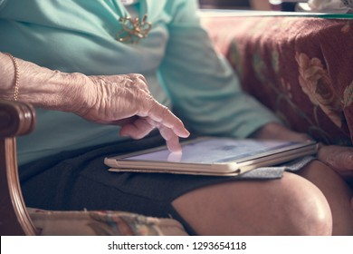 Photograph of an old woman reading newspaper on the tablet. Huelva, Spain