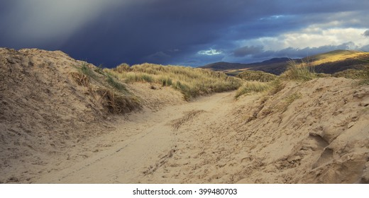 Photograph of a path running through sand dunes with storm clouds beginning to form above.