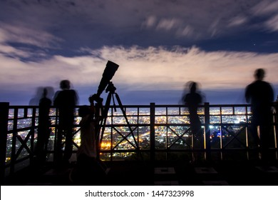 Photograph of photographer setting and taking a photograph at Chiang Mai view point in evening time.