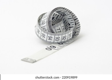 A photograph of a plastic tape measure on a textured white background, with measurements in centimetres and inches.