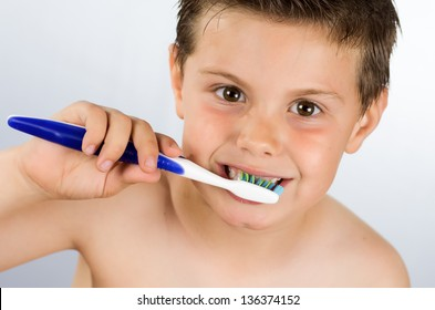 photograph of portrait of a boy brushing his teeth