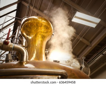 A photograph of a pot still in a whiskey distillery. Steam is rising from the still to the top of warehouse as the still is going through a distillation process.