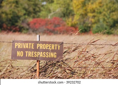 A photograph of a private property no trespassing sign posted on a fence in a Oklahoma field setting.