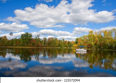 Photograph of a quiet and remote northwoods lake on a beautiful autumn day with clouds reflected in the still blue waters while a pontoon boat of sightseers slowly motors by.