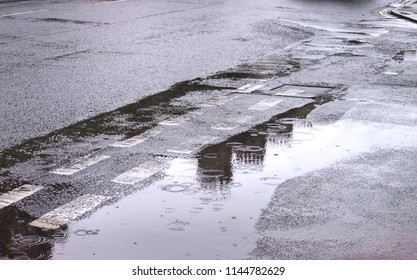 A photograph of the reflection in the water of chimney stacks from a tenement building in Edinburgh in large puddles on a road following storms.