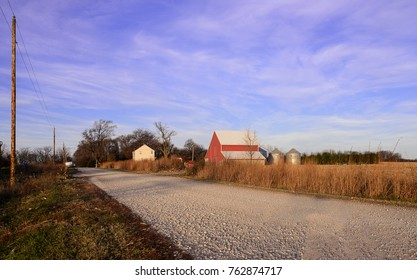 A photograph of a rural Midwest landscape of a farmhouse in Autumn.