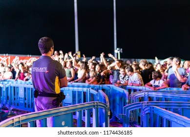 Photograph of a security guard in front of an audience with different colors by the spotlights on the music party that made the main forty in the port of Mao - Mahón, Menorca, Spain, Europe. August 31
