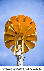 photograph of several multi directional round yellow amplified emergency sirens on top of a pole in a small town