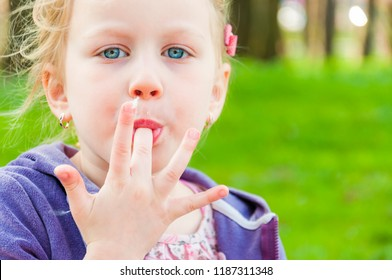 The photograph shows blue-eyed blonde girl that sucking candy-floss fingers one after another and making it with love and inherent to children passion.
