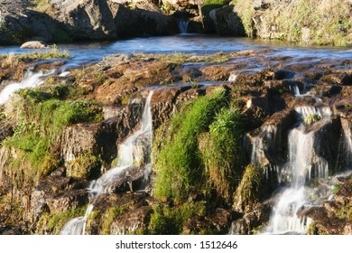 Photograph of small river, flowing, waterfalls, lush green vegetation and genuine tranquil atmosphere