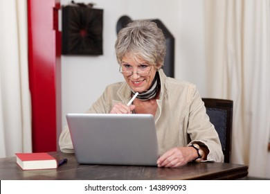 Photograph of smiling senior female using modern technology, working on laptop.