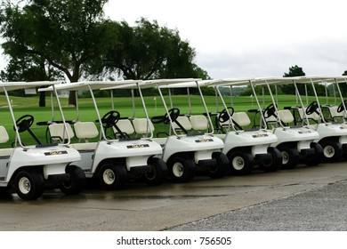 A photograph taken of golf carts parked in a row waiting for the rain to clear.