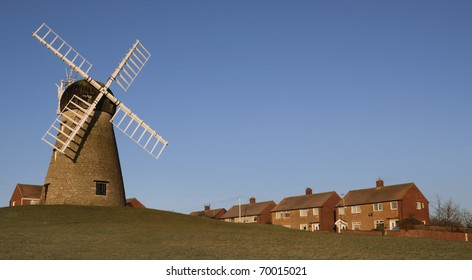 Photograph of a traditional windmill sited close to a residential area.