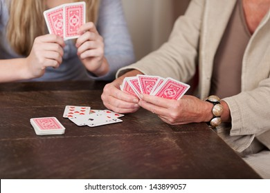 Photograph of two females playing cards together.