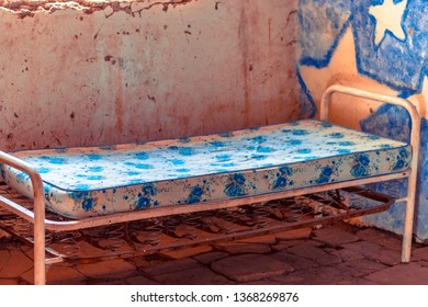 Photograph of a very old bed, made only of metal structure and where you can see the rust. The passage of time and abandonment is notorious