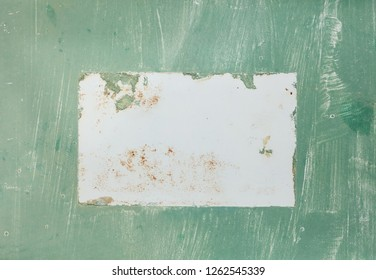 A photograph of weathered green paint on metal with white brush stokes and rust in a horizontal presentation