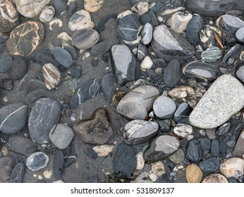 A photograph of wet rocks, at the side of a river forming a pattern
