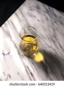 A photograph of a whiskey glass filled with whiskey. The shot is taken from above with light streaming through the glass, consequently creating a deep golden and dark shadow.