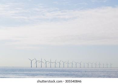 Photograph of wind power plants in the morning haze close to Copenhagen, Denmark.