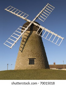 Photograph of a windmill, a traditional form of renewable energy.