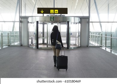 Photograph of a woman walking towards the exit of the airport to take a taxi or bus.