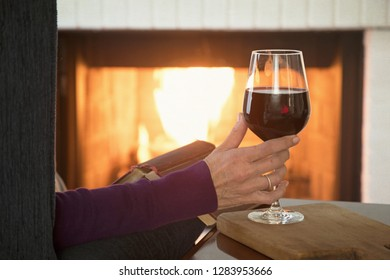 Photograph of a woman's hand grasping a glass of red wine in front of the fireplace.