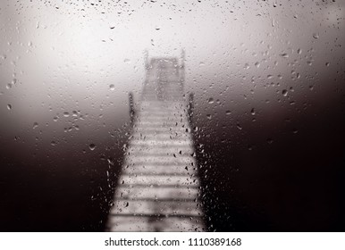Photograph of a wooden dock on a quiet lake on a rainy day in black & white.
