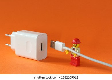 A photograph of working man fixing mobile phone charger isolated on orange background. Editorial close up image of Lego minifiure rapair tech items.