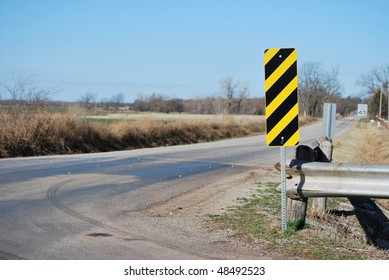 A photograph of a yellow and black guard rail sign.
