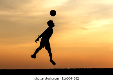 Photograph of young athlete silhouetted against the sunset heads a soccer ball at  in this concept photo.