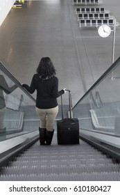 Photograph of a young woman coming down the escalator with suitcase at the airport.