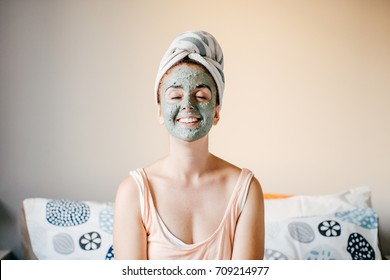 Photograph of a young woman using a mask to improve her skin and relax at home. Lifestyle Portrait