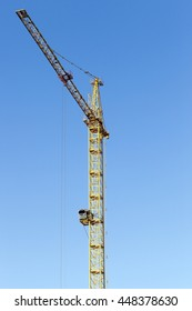 photographed close-up construction cranes during construction of a new multi-storey apartment building, blue sky,