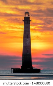 Photographed from Folly Beach, a colorful sunrise sky silhouettes the historic Morris Island Lighthouse on the Atlantic coast near Charleston, South Carolina.