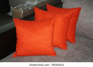 Photographed several orange pillows on a modern bed, select focus